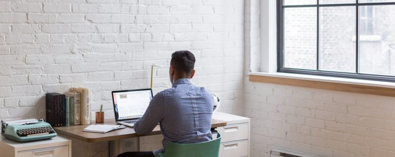 Човек, работещ на компютър